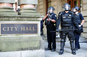 Police guard the entrance to City Hall after removing protesters against the new police union contract in Portland, Ore., on October 12, 2016. the contract was approved by City Council this morning. (Photo by Alex Milan Tracy) [Photo via Newscom]